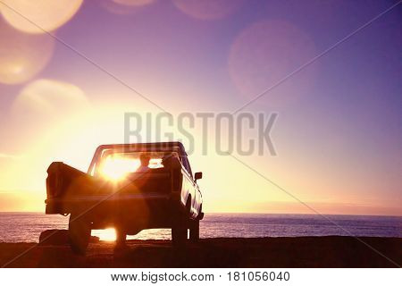 Rear view of young couple in pick-up truck parked in front of ocean enjoying sunset