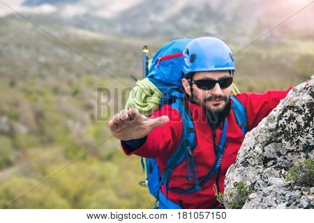 Climbers reaches the top of mountain peak search help hand. Climbing and mountaineering sport