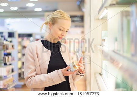 Elegant blond young woman choosing perfume in retail store. Beautiful blond lady testing and buying cosmetics in a beauty store.