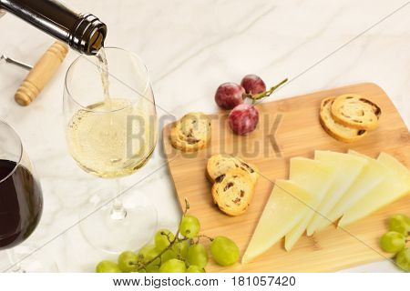White wine poured into a glass at a tasting, with cheese, bread, and grapes. Selective focus