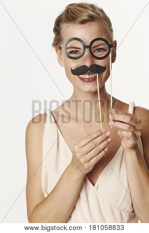 Beautiful woman playing with mustache and spectacles disguise
