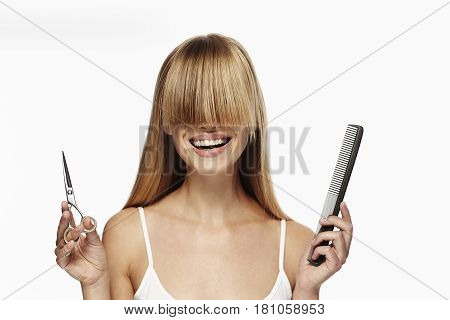 Blonde haired woman with long fringe and scissors