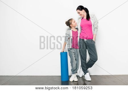 Happy Mother And Daughter In Sportswear Standing With Yoga Mat And Looking At Each Other