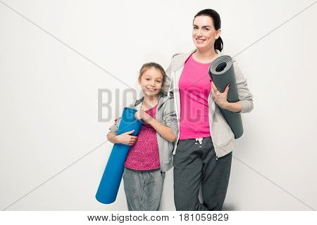 Happy Mother And Daughter In Sportswear Holding Yoga Mats And Smiling At Camera