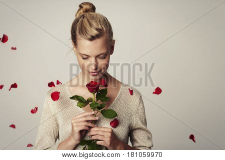 Beautiful woman with red rose petals studio