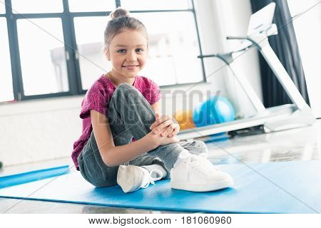 Adorable Girl In Pink Shirt Sitting On Yoga Mat In Gym