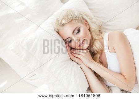 Beautiful Young Woman Sleeping On A White Bed .