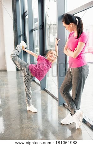 Mother And Daughter In Pink Shirts In Gym, Girl Stretching At Window