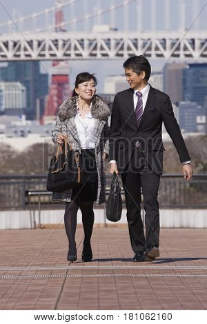 Asian businesspeople walking outdoors