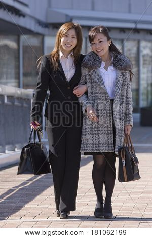 Asian businesswomen standing arm in arm