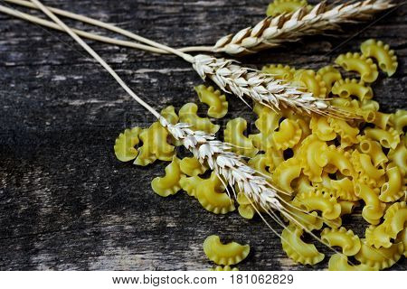 Ears of wheat on a brown wooden background. Near the scattered ears of wheat pasta.