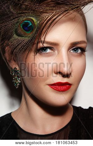 Close-up portrait of young beautiful glamorous woman with red lipstick and peacock feather