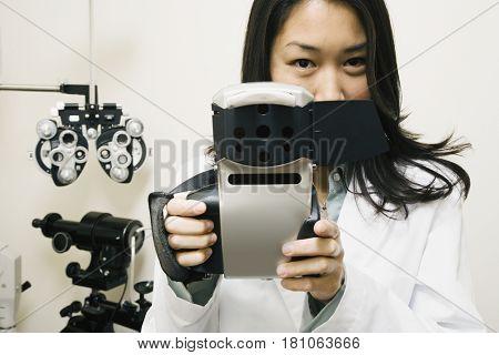 Asian female optometrist holding equipment