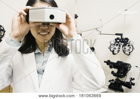 Asian female optometrist looking through equipment