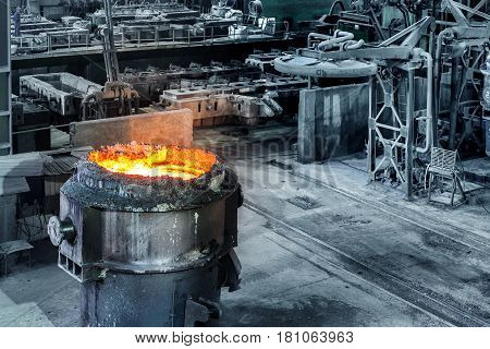 Large steel mills in the production workshop filled with molten steel ladle
