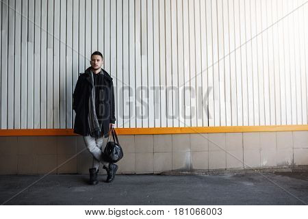 Stylish man in fashion fall look standing against wall. Minimalizm style. Trendy photography style.