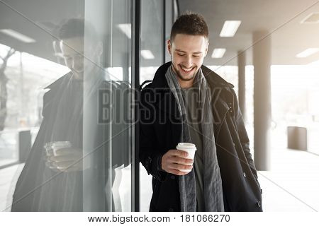 Man in coat stopped to have some coffee, relaxing with hot drink, leaning to wall.