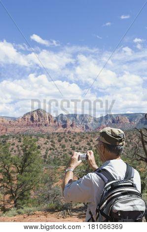 Senior man taking photograph of desert landscape