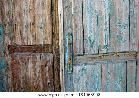 Closeup of metal door handle on old obsolete weathered wooden door with cracked blue paint