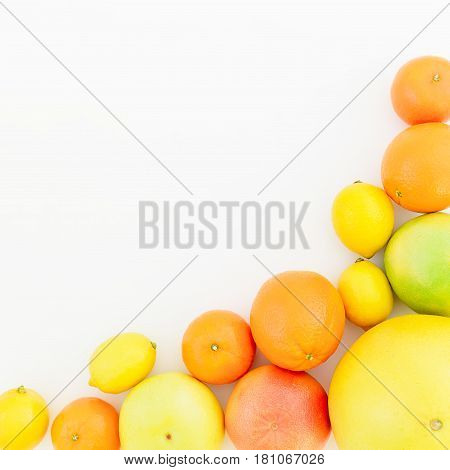 Fruit frame of lemon, orange, mandarin, grapefruit and sweetie on white background. Flat lay, top view.
