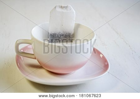 Closeup teabag put in white ceramic teacup on white saucer