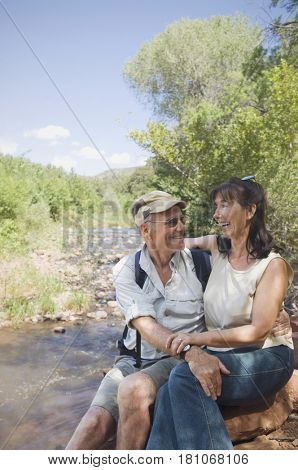Multi-ethnic senior couple hugging next to stream