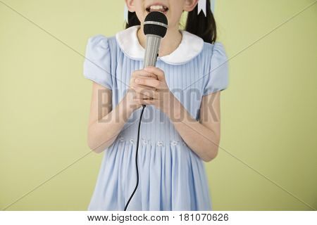 Asian girl singing into microphone