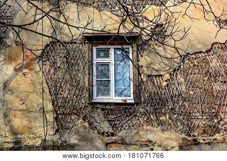 Modern plastic window in obsolete weathered wall