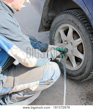 employee of the tire to loosen the wheel