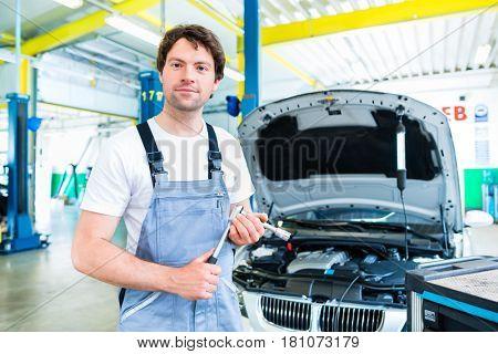 Auto mechanic repairing car engine in workshop
