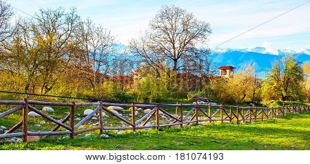 Spring landscape with the wooden fence, trees, tower of chalet and snowy peaks of mountains in Bansko, Bulgaria
