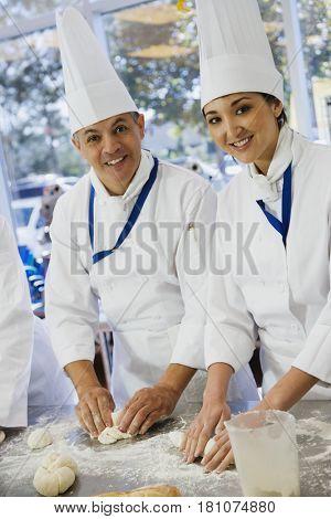 Multi-ethnic bakers rolling dough