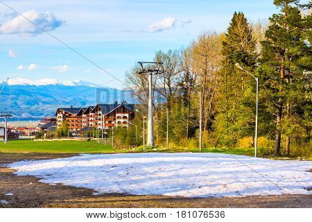 Spring landscape with trees, chalet and snowy peaks of mountains in Bansko, Bulgaria