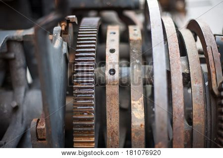 Old rusty printing machine complex mechanism of metal with close up details
