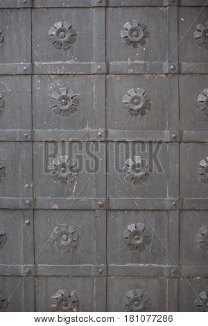 A large massive ancient metal wrought-iron black door with ornamentation