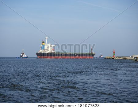 bulk carrier and tug ship on sky background