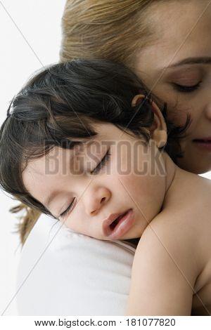 Hispanic baby sleeping on mother's shoulder