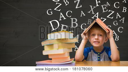 Digital composite of Boy with book on head against letters flying in background