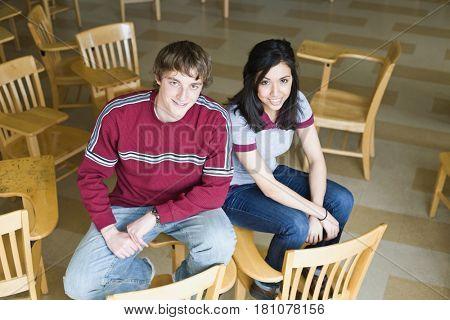 Multi-ethnic college students sitting on desks