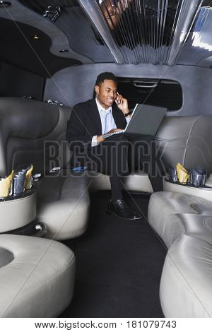African businessman working in limousine