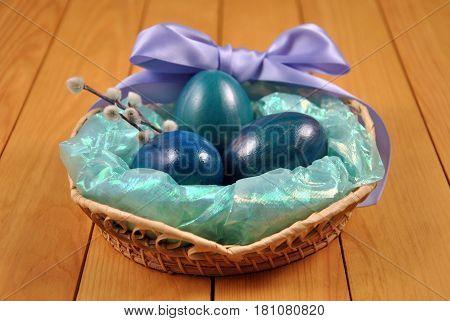 Сине-зеленый натюрморт из яиц и вербы с сиреневым бантом в плетеной корзине