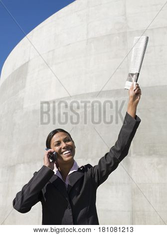 Indian businesswoman talking on cell phone with newspaper