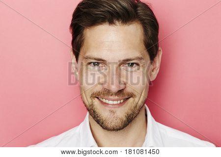 Happy chap on pink background studio shot