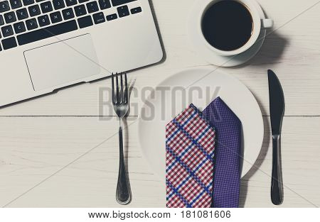 Diet or lack of money concept - no food at business lunch in the office. Top view of working space at white wooden desk, empty plate with tie, americano coffee cup and cutlery near laptop
