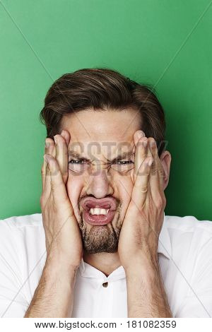 Man pulling funny squashed face in studio