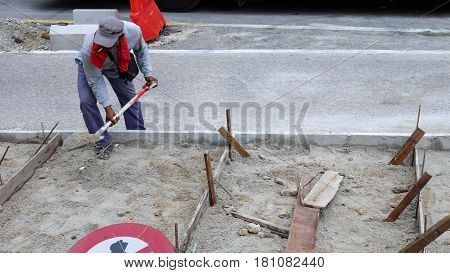 Worker Working Digs A Hole With A Shvel And Spade In The Sand At Road Construction Site. Road Constr
