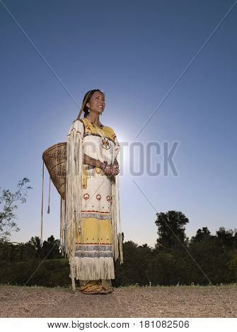 Native American woman in traditional clothing with hand-made basket