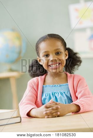 Mixed race girl at desk in classroom