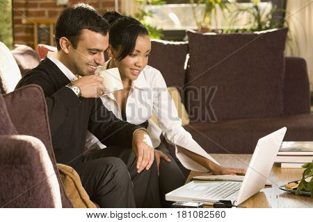 Mixed race couple working on laptop in living room