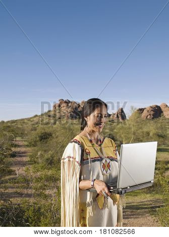 Native American woman in traditional clothing with laptop outdoors